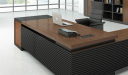 walnut wood office table with grooved base and wirebox on desktop