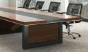 wooden meeting table with black leather chairs