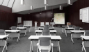 classroom with white tables and gray chairs